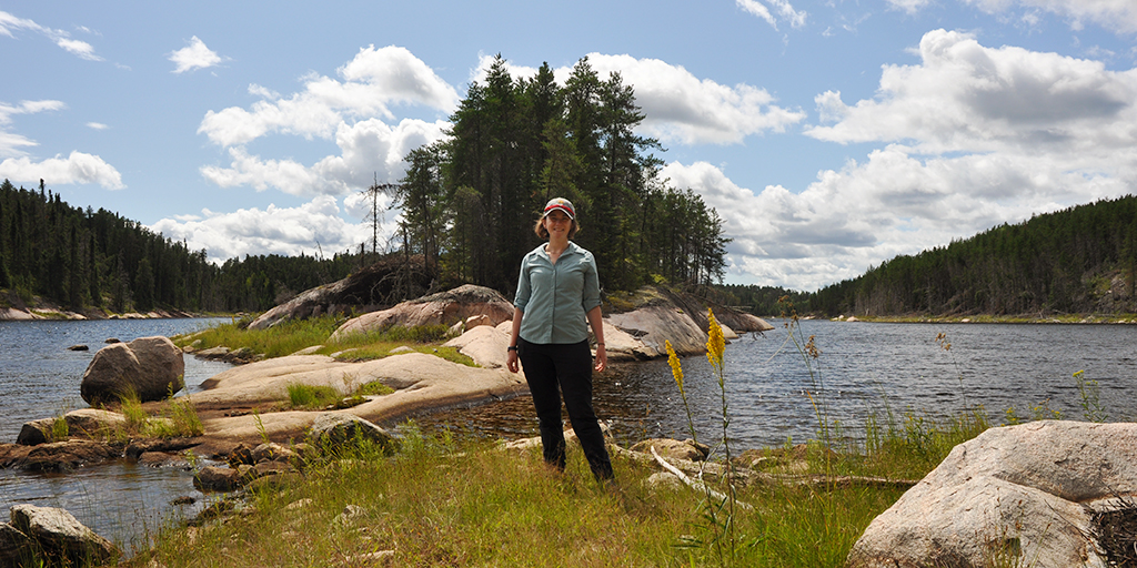 A woman standing on an island in a lake