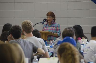 Edna Andrews speaking in front of a class of students.