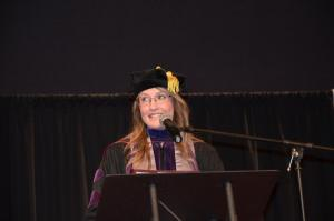 Rebecca Ewing speaking at a podium in graduation regalia